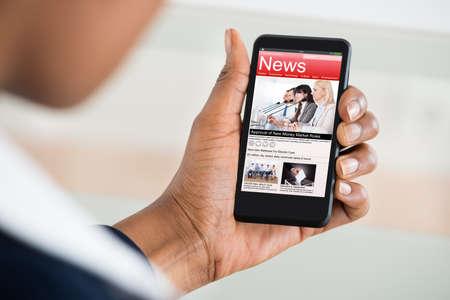 女性の手は、携帯電話でニュースを読むのクローズ アップ 写真素材