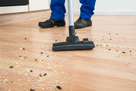 cropped out: Low section of male janitor cleaning floor with vacuum cleaner in kitchen Stock Photo