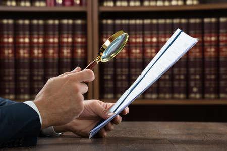 Bebouwd beeld van advocaat onderzoek van documenten met een vergrootglas in de rechtszaal