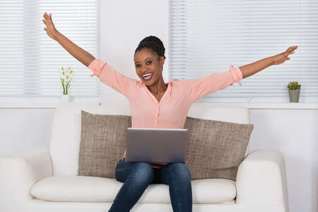 black lady: Portrait Of Excited African Woman Sitting On Sofa With Laptop Stock Photo