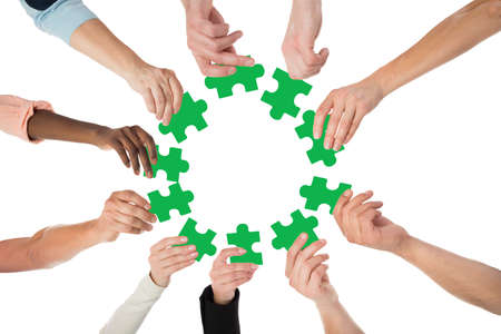 Directly below shot of people holding green jigsaw pieces in huddle against white background