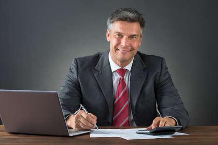 registros contables: Hombre de negocios maduro que controla cuentas con la calculadora y el ordenador portátil en el escritorio contra el fondo gris