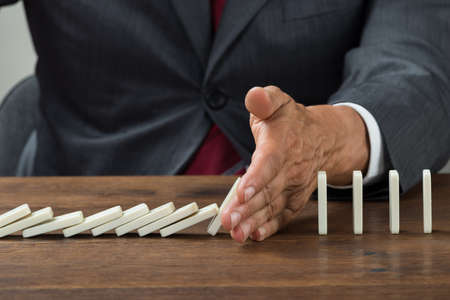 domino: Midsection of businessman stopping dominoes falling on wooden desk