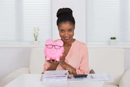 happy worker: Smiling Young African Woman Holding Piggybank With Eyeglasses