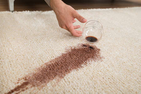 addictive drinking: Cropped hand of drunk man spilling red wine on rug