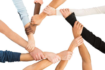 unity: Directly above shot of people holding each others hand in showing unity against white background