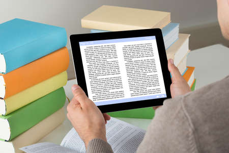 ereader: High angle view of male student holding ereader while studying at desk Stock Photo