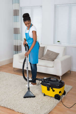 Smiling Young African Woman Cleaning Carpet With Vacuum Cleaner