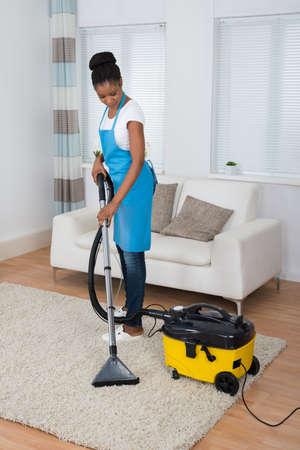 mujer limpiando: Sonriendo Mujer africana joven que limpia la alfombra con el aspirador Foto de archivo