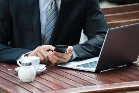 people on computers: Close-up Of Man Sitting On Table Using Phone Stock Photo
