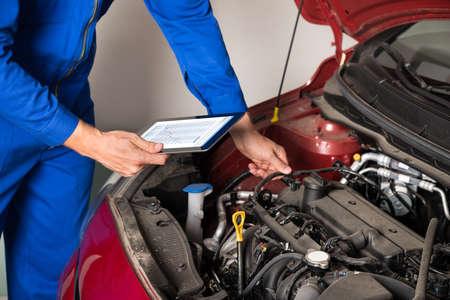ガレージで車のエンジンを調べながらメカニックを使用してデジタル タブレットのクローズ アップ