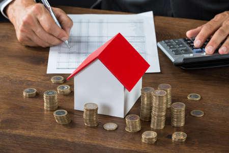 pagando: Imagen recortada de hombre de negocios c�lculo del impuesto por el modelo de casa y las pilas de monedas en la mesa