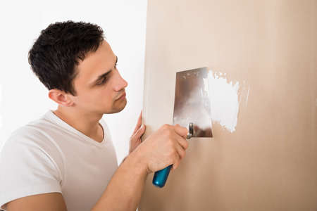putty knives: Young man using putty knife on white wall at home