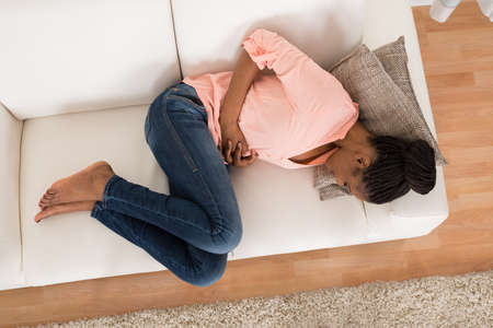 constipation symptom: High Angle View Of Young African Woman With Stomach Ache Lying On Sofa Stock Photo