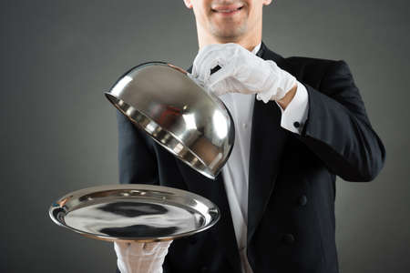 Midsection of waiter holding cloche over empty tray while standing against gray background