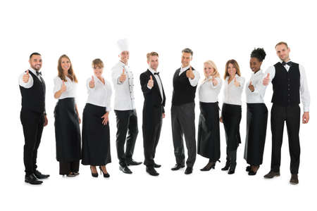 hospitality industry: Full length portrait of confident restaurant staff standing in row against white background