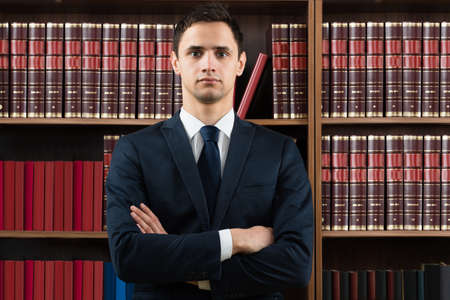 lawyers: Portrait of confident male lawyer standing arms crossed against bookshelf in courtroom Stock Photo