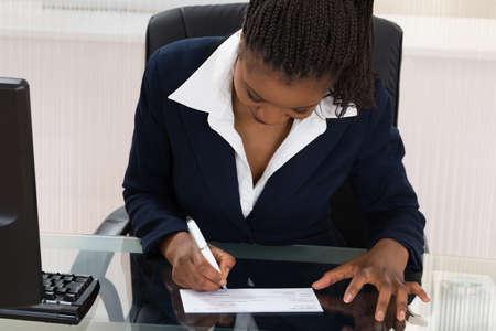 Jonge Afrikaanse zakenvrouw ondertekening Cheque bij Bureau