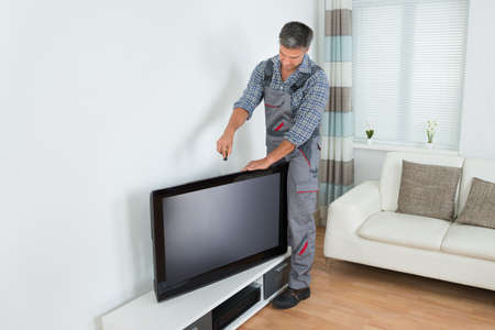 service technician: Full length of male technician installing television at home