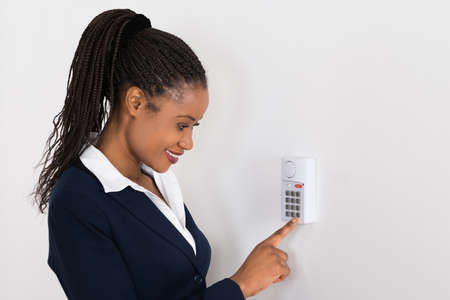 lock: Close-up Of A Young African Businesswoman Pressing Button On Security System Stock Photo