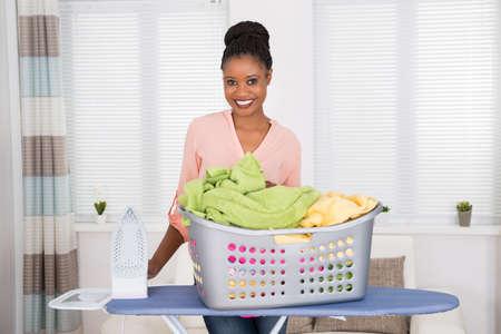 Lächelnde junge afrikanische Frau mit Eisen und Korb voller Kleidung Standard-Bild - 48226391