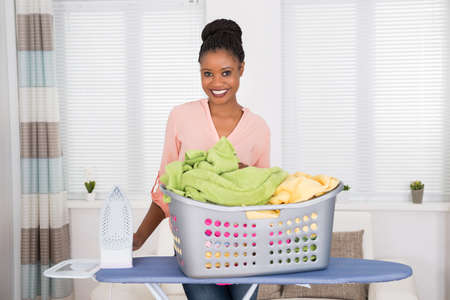 african basket: Smiling Young African Woman With Iron And Basket Full Of Clothes
