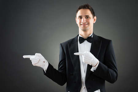 hospitality staff: Portrait of confident waiter presenting invisible product against gray background