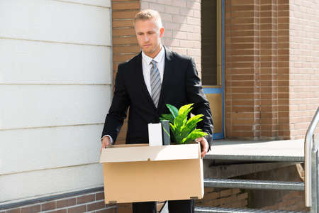 transferred: Disappointed Businessman Standing With Cardboard Box Outside Office Stock Photo