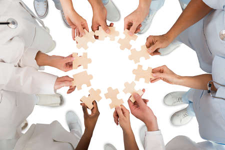 Directly above shot of medical team holding blue jigsaw pieces in huddle against white background Stockfoto
