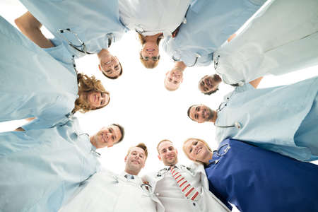directly below: Directly below portrait of confident medical team standing in huddle against white background