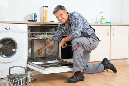 Full length of repairman repairing dishwasher with screwdriver in kitchen Stock Photo