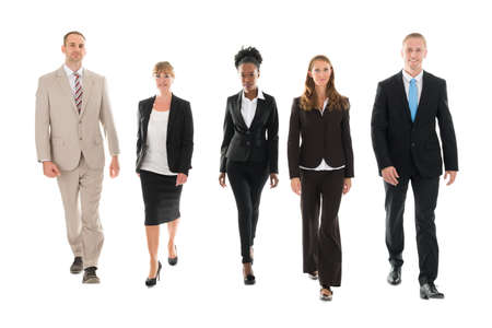 confident business woman: Full length portrait of confident business team walking against white background