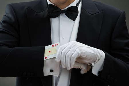 magie: Midsection magicien effectuant tour de magie avec des cartes sur fond gris Banque d'images