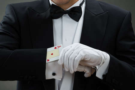 magia: Sección media de mago realiza truco de magia con cartas contra el fondo gris
