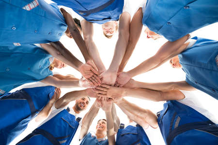 Cleaning team: Directly below shot of janitors stacking hands in huddle against white background Stock Photo