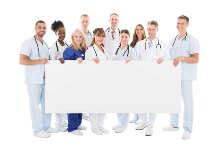 healthcare team: Full length portrait of confident multiethnic medical team holding blank billboard against white background