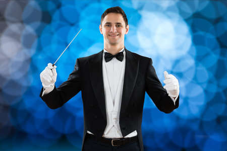 choral: Portrait of happy music conductor holding baton against colored background
