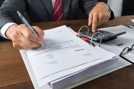 registros contables: hombre de negocios maduro que controla recibos con la calculadora en el escritorio