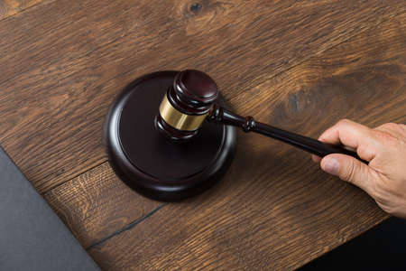 striking: High angle view of male judge striking gavel at table
