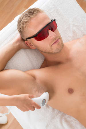 hair treatment: Beautician Giving Laser Epilation Treatment On Mans Armpit Stock Photo
