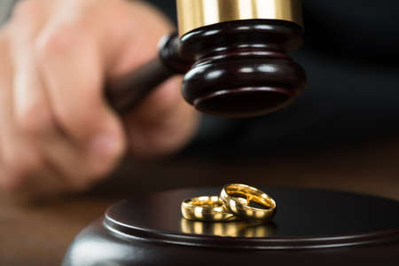 divorce: Imagen recortada de juez de divorcio golpear martillo en anillos de oro en el escritorio en sala