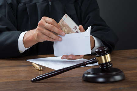 bribe: Midsection of judge removing money from envelope in courtroom