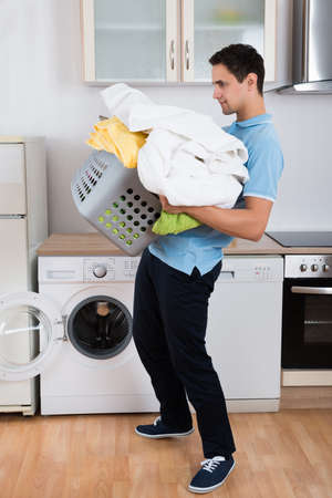 burdened: Young man carrying heavy laundry basket by washing machine at home