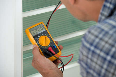 multimeter: Cropped image of male repairman checking fridge with digital multimeter at home