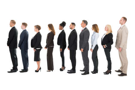 standing businessman: Full length side view of business team standing in row against white background