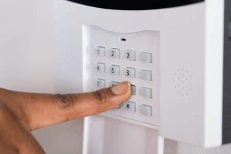 security door: Close-up Of A Persons Hand Entering Code In Security System