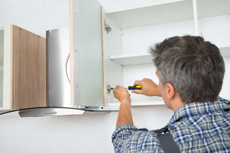 Rear view of serviceman fixing cabinet with screwdriver in kitchen