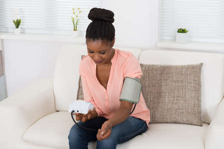 blood: Young African Woman Checking Blood Pressure At Home Stock Photo