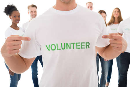 showing: Closeup of man showing volunteer text on tshirt with friends standing over white background Stock Photo
