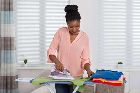 woman ironing: Young African Woman Ironing Clothes At Home